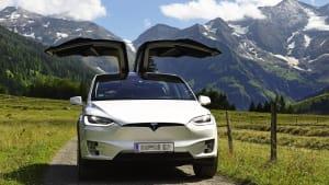 Ein Tesla Model X steht auf eine Weg vor Bergkulisse, mit geöffneten Flügeltüren