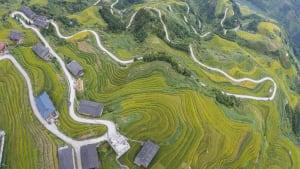 Luftaufnahme von einer Passstrasse, die durch Reisterrassen in Asien führt.