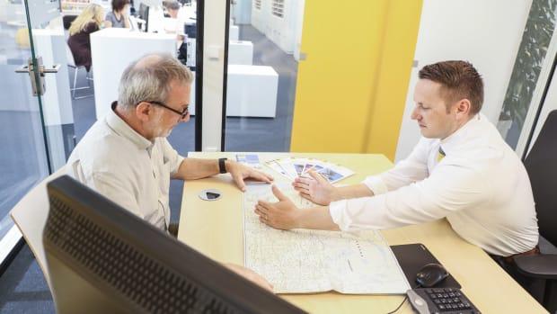 ADAC Touristik-Experte zeigt Mann sein Reiseziel auf einer Karte.