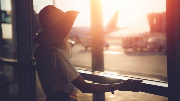 Eine Frau steht am Flughafen und blickt über das Rollfeld