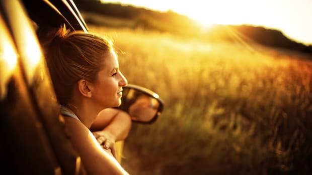 Frau schaut aus dem Autofenster in die Landschaft im Sommer
