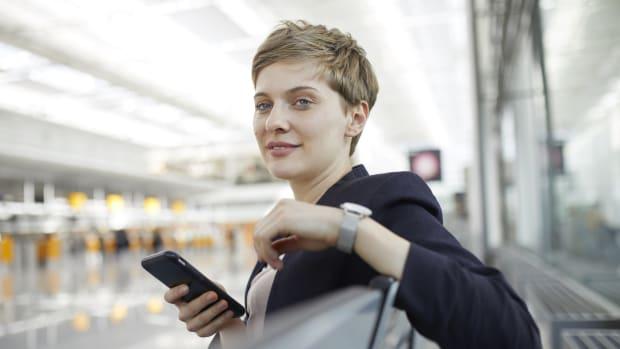 Eine Frau sitzt mit einem Handy in einer Halle am Flughafen
