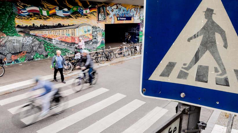 Fahrradfahrer fahren über einen Zebrastreifen während ein Mann gerade darüber geht
