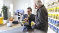 ADAC Mitarbeiter berät älteren Herren im Reisebüro.