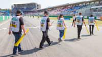 Sportwarte laufen in einer Reihe über die Start- und Zielgerade auf dem Hockenheimring