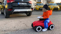 Bobbycar-Dummy fährt hinter einem Auto