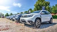 Verschiedene Dacia Modelle stehen auf dem Kiesparkplatz bei einem Autohändler im Sommer