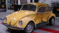 Ein gelber VW Käfer Baujahr 1983 nach einem Crashtest mit eingedellten Türe