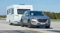 silberner Hyundai Tucson mit Wohnwagen faehrt auf ADAC-Testgelaende