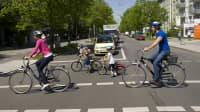 eine Familie überquert mit ihren Rädern eine Strasse