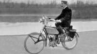 Historische Aufnahmen eines Mannes, der ein Motorrad fährt, dass aussieht, wie ein Fahrrad