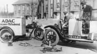 Strassenhilfsdienst repariert ein Auto in den 20ern.
