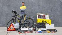 Ein Pannenhelfer mit seinem Fahrrad, Anhänger und Werkzeug