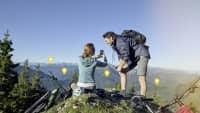 Mann und Frau nutzen Smartphone auf Berggipfel