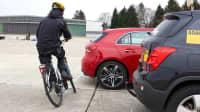 Auto mit Bremsassistent fährt rückwärts während ein Radfahrer naht