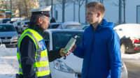 Polizist führt einen Alkoholtest bei einem jungen Autofahrer durch