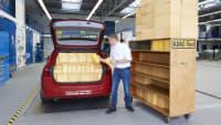 Ein ADAC Mitarbeiter misst das Volumen eines Kofferraumes anhand von Schaumstoffwürfeln.