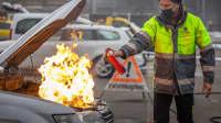 Ein Mann löscht mit dem Handfeuerlöscher einen Brand im Motorraum