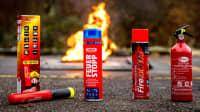 Diverse Handfeuerlöscher für den PKW fotografiert auf Asphalt mit Feuer im Hintergrund