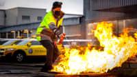 Mann löscht mit einer Löschpatrone bzw Handfeuerlöscher eine Feuerstelle auf Asphalt
