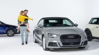Vater trägt seine Tochter, die auf einen grauen Audi zeigt