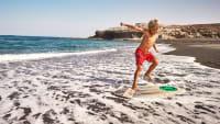 Junge surft auf Skimboard