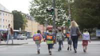 Mehrere Kinder mit Schulranzen überqueren eine Straße in München auf dem Weg zur Schule