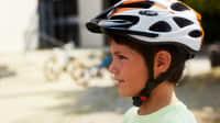 Portraitaufnahme eines Grundschülers mit Fahrradhelm der den Sicherheitsvorschriften genügt