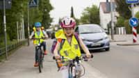 Ein Mädchen mit Fahrrad, Helm und Warneste im Strassenverkehr
