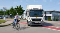 LKW biegt auf einer Straße ab, neben ihm fährt eine Fahrradfahrerin