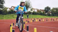 Ein Kind fährt beim ADAC Fahrradturnier sicher durch den Parcour