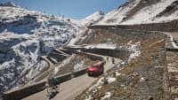 Ein rotes Auto fährt auf einer Passstrasse, auf den Bergen liegt Schnee