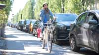 Junge Frau telefoniert mit ihrem Handy während sie Fahrrad fährt