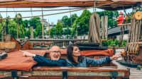 Linda Zervakis und Peter Lohmeyer zeigen nach links und rechts auf einem Hochseekutter im Museumshafen Oevelgönne am Fähranleger Neumühlen