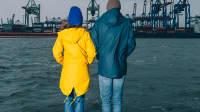Peter Lohmeyer und Linda Zervakis in Rückenansicht im Hamburger Hafen bei Regenwetter