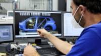 Ein ADAC-Mitarbeiter schaut sich ein Bild des Crashtest Rückhaltesysteme auf einem Computerbildschirm an.