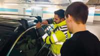 Ein Schlüsseldienst Service Mitarbeiter öffnet ein verschlossenes Auto