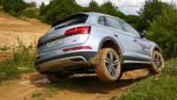 silberner Audi Q5 faehrt durch Gelaende