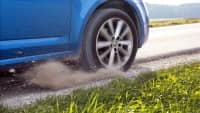 Ein blaues Auto ist auf den Seitenstreifen geraten und bremst