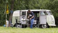 Lars Conrads bereitet vor seinem VW Bulli Frühstück zu