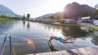 Mann springt in den See vor dem Campingplatz