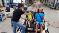 Ein Mann setzt 2 Dummies auf eine Rücksitzbank in der Crashanlage in Landsberg
