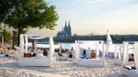Der 689 Cologne Beach Club am Rheinufer in Köln mit weißen Beach Lounges und dem Kölner Dom im Hintergrund