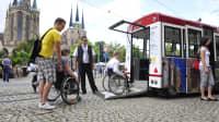 Rollstuhlfahrer steigen mittels einer Rampe in eine Trambahn