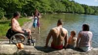 Familie und ein Mann im Rollstuhl sitzen an einem Seee