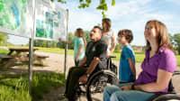 Familie und Mann im Rollstuhl schauen auf ein Schild in einer Landschaft