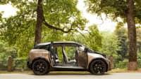 BMW i 3steht mit geöffneten Türen vor Bäumen