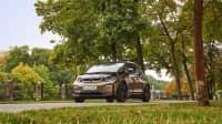 BMW i 3 fährt durch Frühlingslandschaft auf einer Strasse