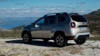 Silberner Dacia Duster steht in Gelaende
