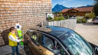 Eine Frau läd ein E-Auto in einer Einfahrt